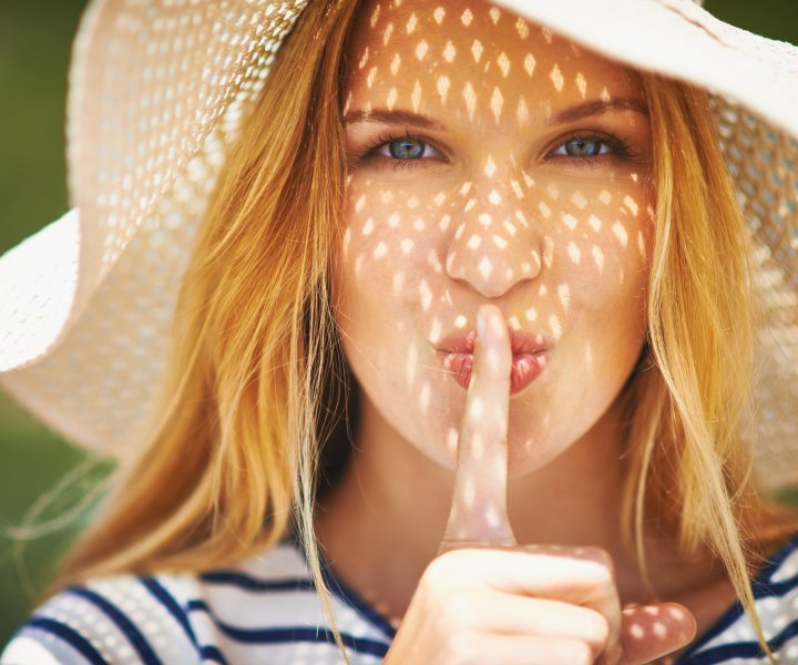 Pretty woman in sunhat looking at camera and making shh gesture